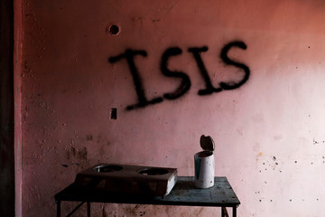 "Burnt kitchen items are seen in front of a wall spray-painted with the word ""ISIS"" in a home in the most affected war-torn area of Marawi City"
