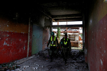 Safety managers carry equipment for bomb detection during a scheduled visit for internally displaced people in the most affected war-torn area of Marawi City