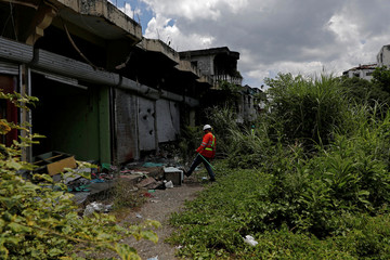 A safety manager carries equipment for bomb detection during a scheduled visit for internally displaced people in the most affected war-torn area of Marawi City