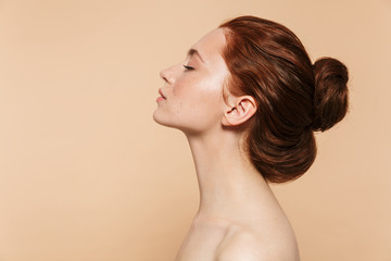 Young redhead woman posing isolated over beige wall background. Wall mural