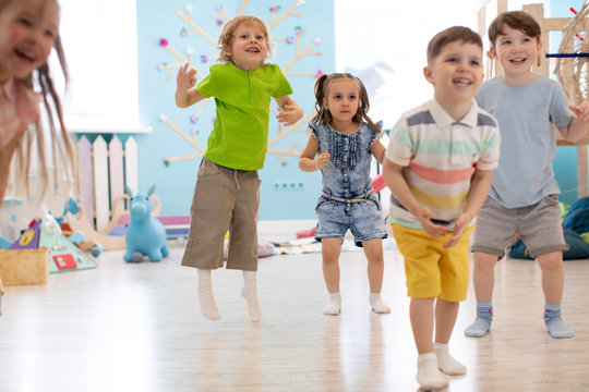 Group of happy kids playing and jumping in daycare