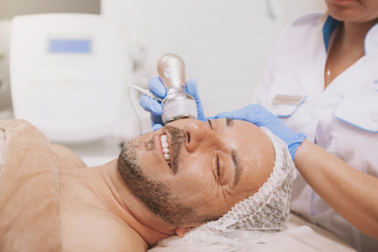 Relaxed handsome mature man smiling, getting ultrasound cavitation treatment by professional cosmetologist. Beautician using hardware cosmetology equipment on a male clienteatment