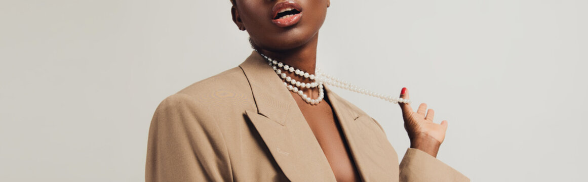 cropped view of seductive african american woman in beige jacket and necklace isolated on grey