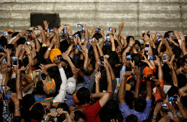 Supporters of Indian Prime Minister Narendra Modi use their mobile phones to click his pictures as he addresses them after the election results at the Bharatiya Janata Party (BJP) headquarter in New Delhi