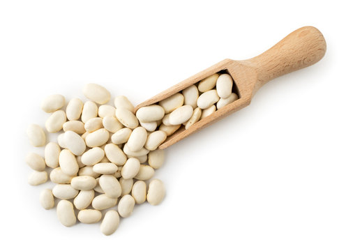 White beans spilled from a wooden spoon. The form of the top.