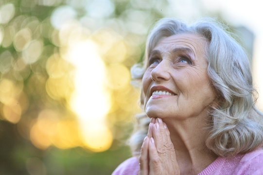 Close up portrait of cute senior woman praying outdoors