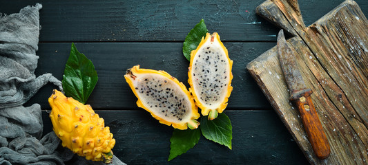 Yellow Pytahya on a black background. Fruit Dragon. Tropical Fruits. Top view. Free space for text.