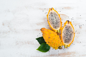 Yellow Dragon Fruit on a white wooden background. Pitahaya Tropical Fruits. Top view. Free space for text.