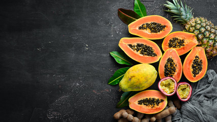 Papaya fruit on a wooden background. Tropical Fruits. Top view. Free space for text.