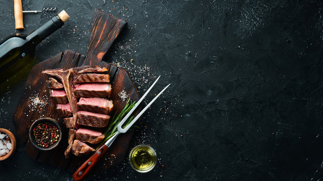 Beef T-Bone steak on a black table. Top view. Free space for text.