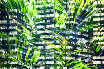 Fototapete - lush green plants and skyscrapers windows double exposure - sustainable green energy