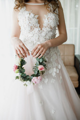 Beautiful wreath of flowers in the hands of the bride.