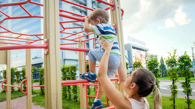 Portriat of young mother supporting and holding her 3 years old child son on metal ladder at children playground in park