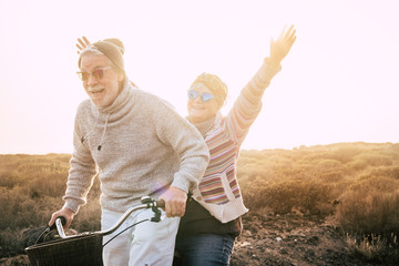 Happiness for active senior retired people lifestyle concept - joy old aged caucasian couple riding together a bika laughing and smiling a lot and having fun - outdoor leisure activity - sunset