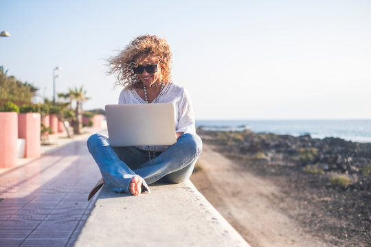 Cheerful beautiful blonde curly people young adult woman sitting outdoor with sea and sky in background working with tablet computer internet connected - freedom from office concept