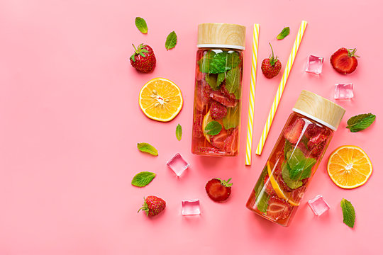 Strawberry infused water, cocktail, lemonade or tea. Summer iced cold drink with strawberry, lemon and lef of mint on pink background. Flat lay. Top view.