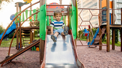Photo of adorable smiling boy climbing and riding on slide. Active child having fun and playing at park