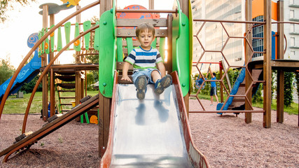 Photo of cute 3 years old toddler boy climbing and riding on big slide on children playground at park