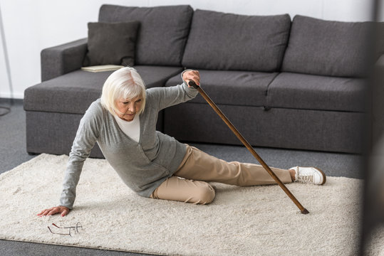 suffering senior woman with heart attack on carpet