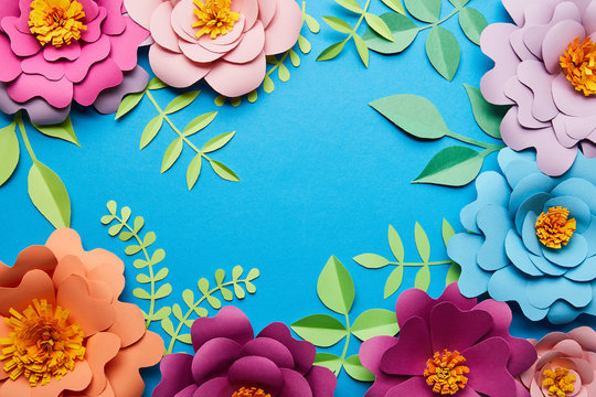 top view of multicolored paper cut flowers with leaves on blue background with copy space