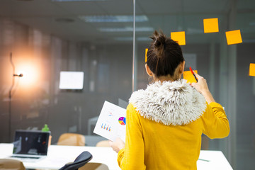 Rear view of businesswoman sticking colorful adhesive notes on window