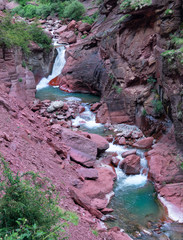 Refreshing emerald colored river flows through the red gorge in the French Alps.