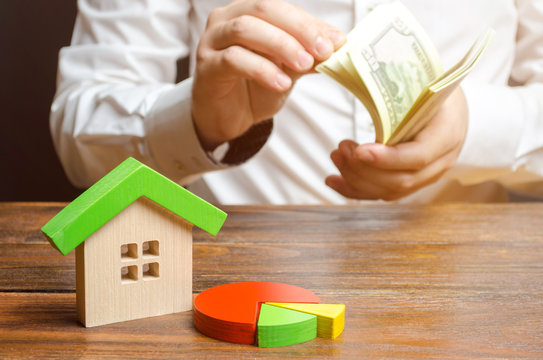 House figurine and pie chart on the background of a man counting money. Micromanagement and cost structure for maintaining a home and paying bills. Buying a house in installments, credit.