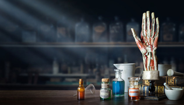 Vintage layout of a man's hand, old medical glass bottles, antique medical tools on the background of a medical office. Old medical, education and science background.