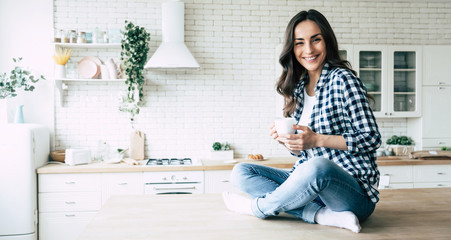 Cute lovely young woman in casual wear with coffee cup in hands is sitting on table in kitchen and relaxing.