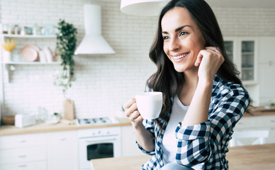 Cute lovely young woman in casual wear with coffee cup in hands is sitting on table in kitchen and relaxing. Wall mural
