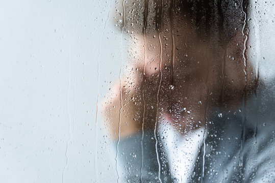 selective focus of crying man behind wet window