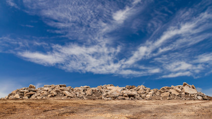 Concrete debris pile with cloudy sky in the background.