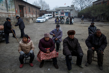 Locals wait for the start of a Chinese opera performance that Xinyuan Steel put on for locals and employees in Anyang