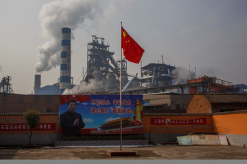 A poster showing Chinese President Xi Jinping is seen in front of the Xinyuan Steel plant in Anyang
