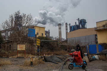 A woman rides a scooter past a steel plant in Anyang