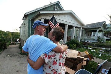 Gwen McGeorge hugs her husband in front of her home following a tornado in Jefferson City