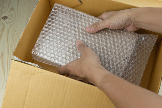 hand of man hold Bubbles covering the box by bubble wrap for protection product