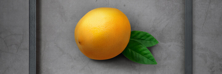 Bright, juicy fresh lemon in a wooden frame on a gray cement background.
