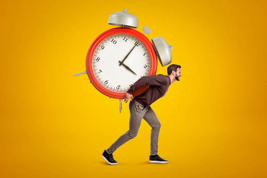 Side view of young handsome man carrying huge alarm clock on his back on yellow gradient background.