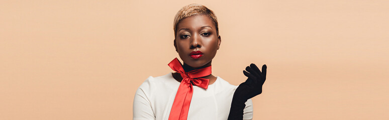 fashionable attractive african american girl posing in red scarf and black gloves isolated on beige Wall mural