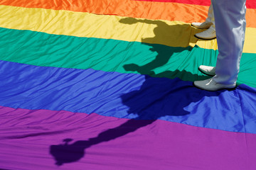Gay newlyweds walk on a giant rainbow flag at a pro same-sex marriage party after registering their marriage in Taipei