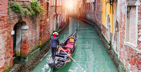 Tuinposter Venice Venetian gondolier punting gondola through green canal waters of Venice Italy