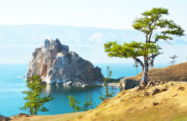 Baikal Lake. Olkhon Island on a summer day. The famous Burkhan Сape, the magic Shamanka Rock and the Wish larch tree with colorful ribbons of tourists in the sunset light