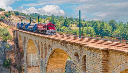 Red passenger diesel train moving at the bridge - Varda railway bridge, Adana Turkey