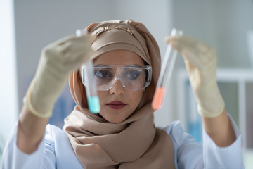 Chemist wearing stylish headscarf holding test tubes with chemicals