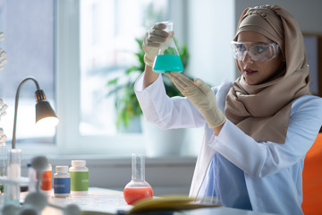Dark-eyed chemist holding chemical glass with blue liquid
