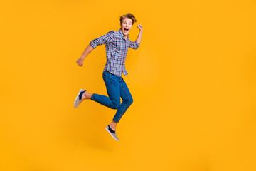 Wall Mural - Full length body size view portrait of nice attractive cheerful cheery optimistic guy in checked shirt having fun running fast hurry rush isolated over bright vivid shine yellow background