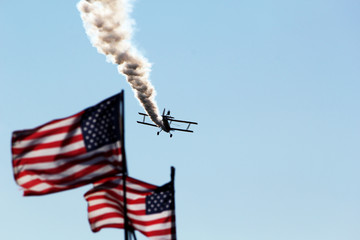 american flags with airplane in sky