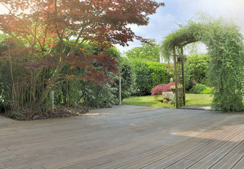 wooden terrace in a garden with japanese maple foliage