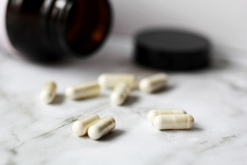 pills and bottle on marble table background
